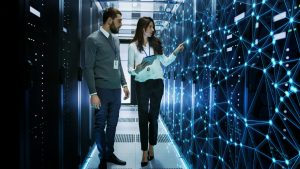 AdobeStock 200146345 300x169 - Female and Male IT Engineers Discussing Technical Details in a Working Data Center/ Server Room with Internet Connection Visualisation.